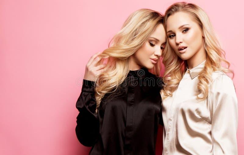 Twee mooie jonge vrouwen in vrijetijdskleding die over roze achtergrond stellen stock afbeeldingen