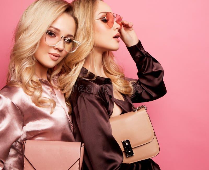 Twee mooie jonge vrouwen in vrijetijdskleding die over roze achtergrond stellen royalty-vrije stock afbeeldingen