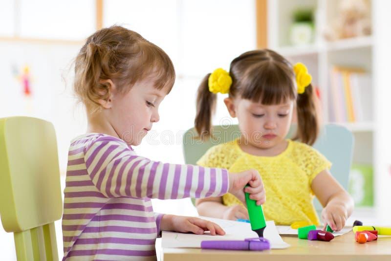 Twee mooie kinderenmeisjes trekken in kleuterschool of kleuterschool stock foto's