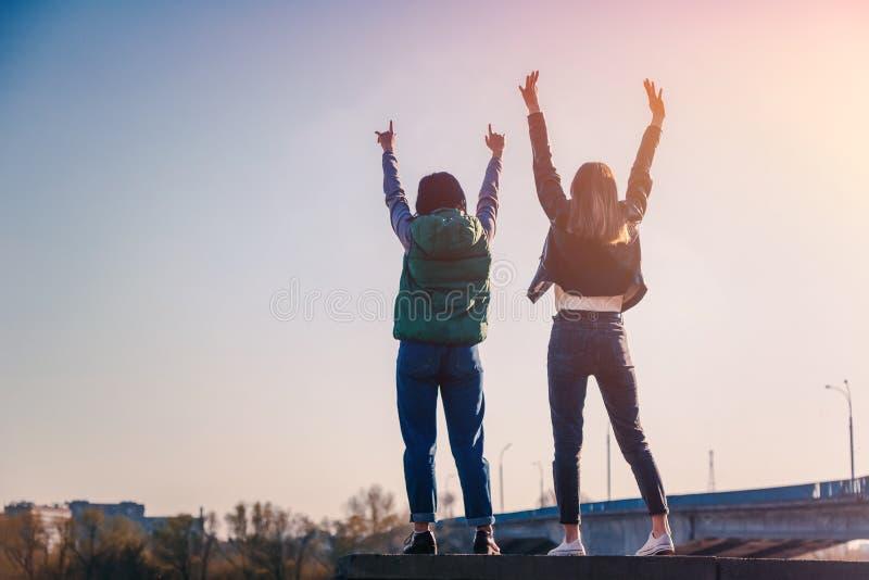 Twee mooie koele tieners 15-16 jaar oude, beste vrienden die pret, met hun omhoog handen hebben royalty-vrije stock afbeeldingen