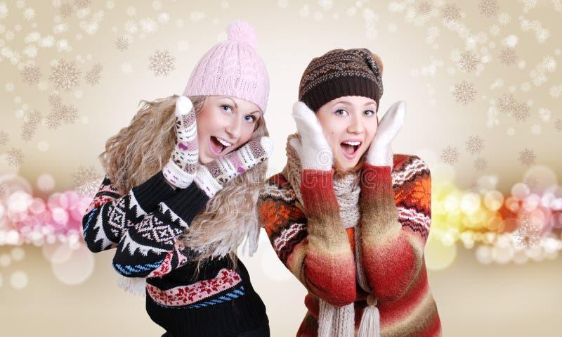Twee mooie lachende meisjes in de winterkleren stock afbeelding