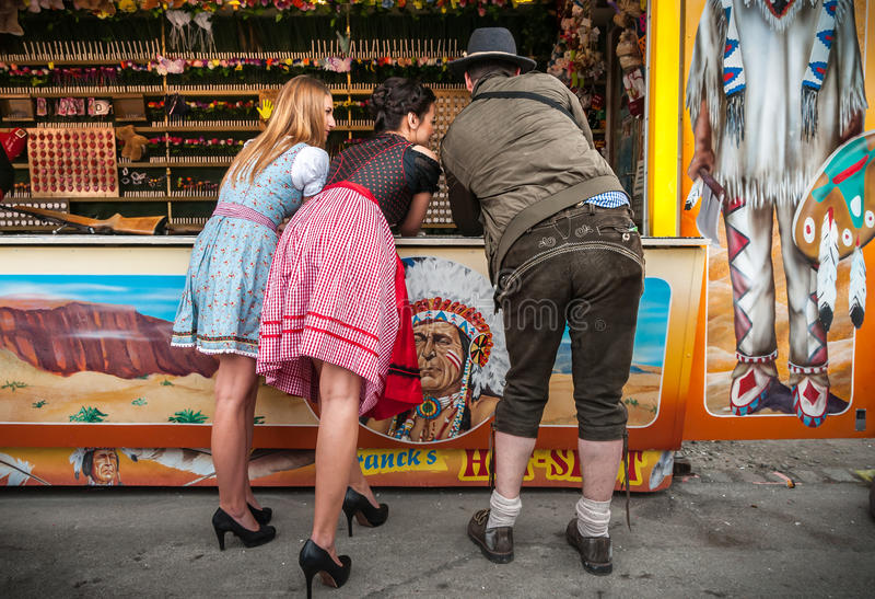 Twee mooie meisjes, één mens die schietend spelen en hebbend pret bij het Duitse traditioneel Dragen van funfairoktoberfest spele royalty-vrije stock fotografie