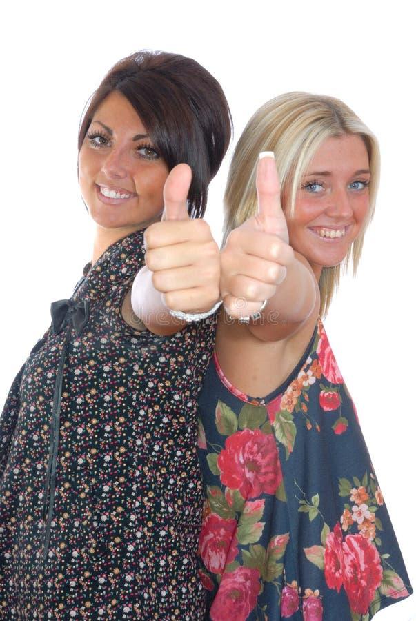 Twee mooie meisjes beduimelt omhoog royalty-vrije stock foto's