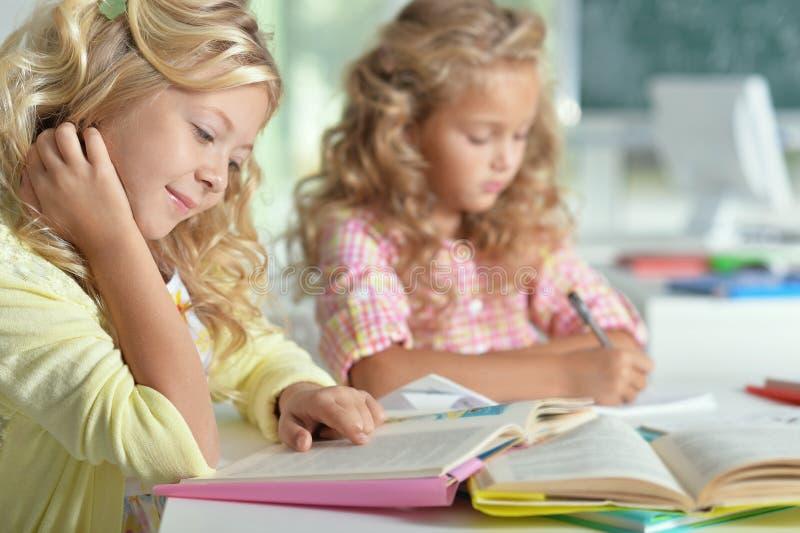 Twee mooie meisjes bij klasse gelezen boek en het schrijven bij niet royalty-vrije stock afbeeldingen