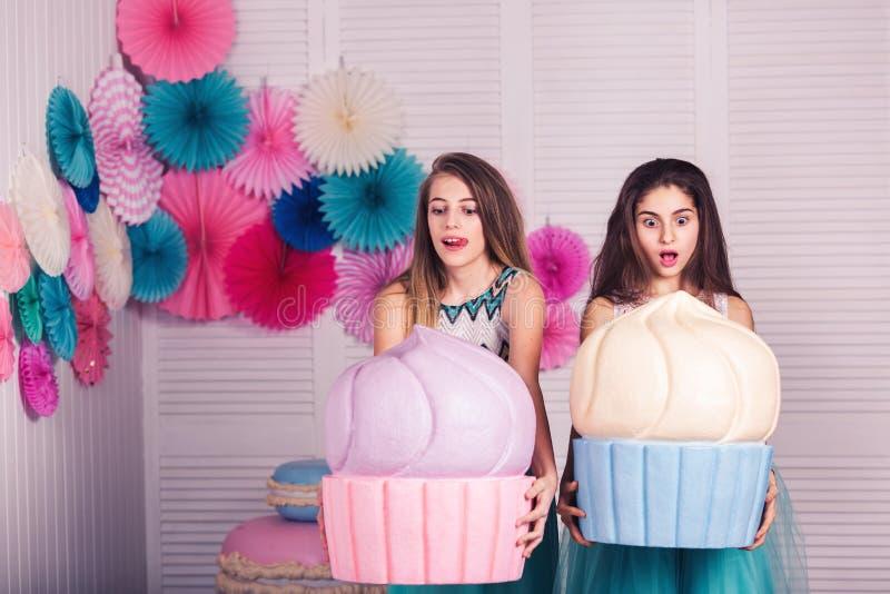 Twee mooie meisjes in blauwe kledingsgreep in hun handen reusachtige cakes Emoties: hongerig de ongelooflijke schok, wauw, wil et royalty-vrije stock foto