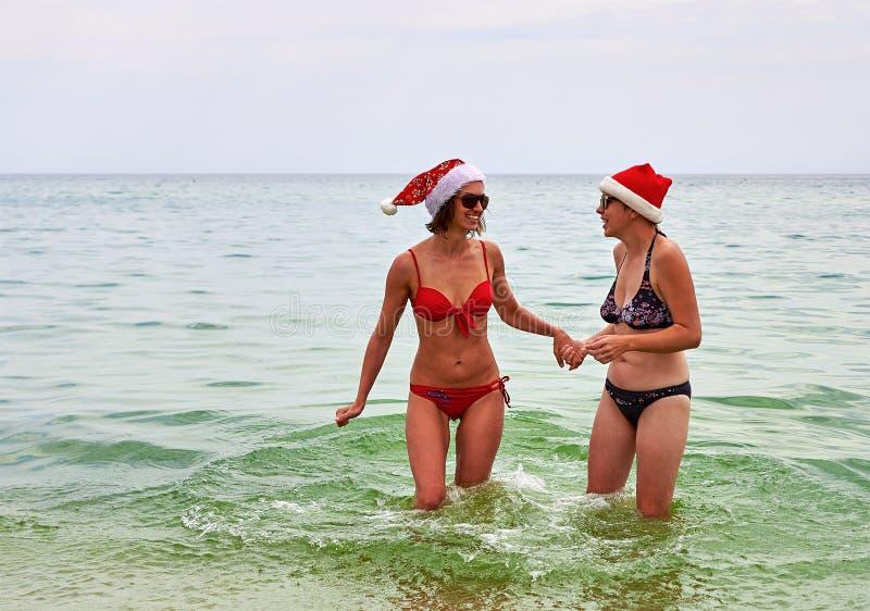 Twee mooie meisjes in de hoed van de Kerstmiskerstman bij het strand royalty-vrije stock fotografie