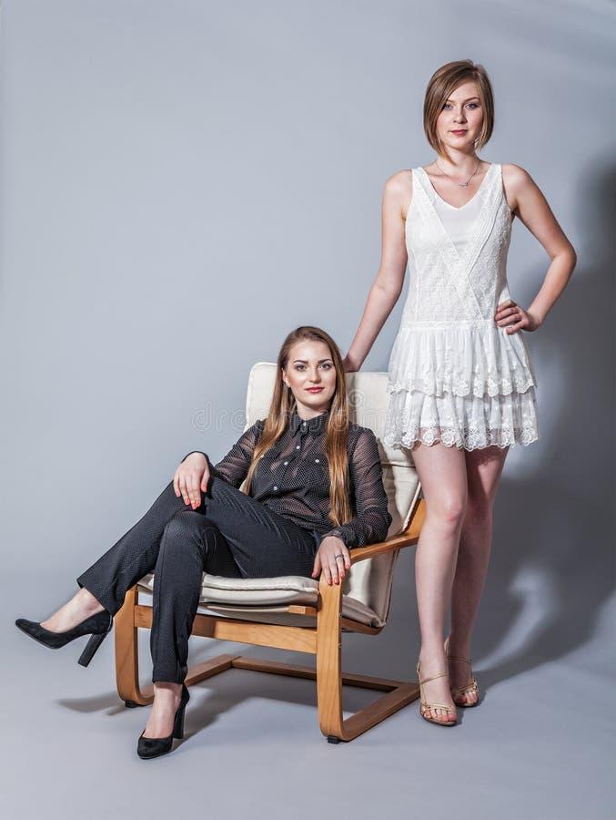 Twee mooie meisjes die in de studio stellen stock afbeeldingen