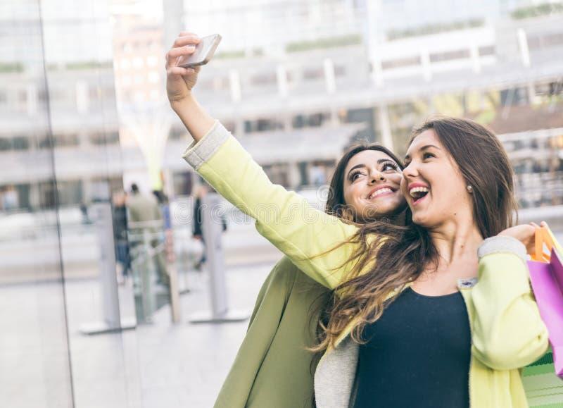 Twee mooie meisjes die het winkelen in het stadscentrum maken en takin royalty-vrije stock afbeeldingen