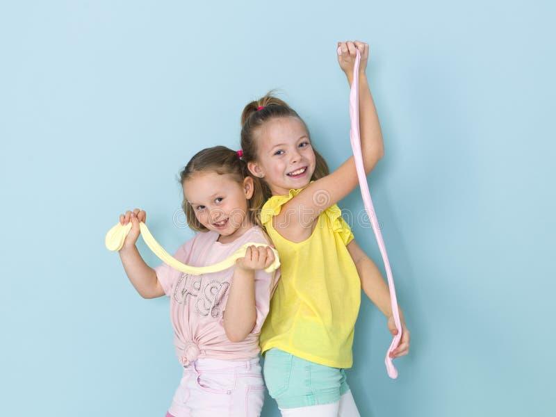 Twee mooie meisjes die met eigengemaakt slijm spelen en heel wat pret voor blauwe achtergrond hebben royalty-vrije stock fotografie