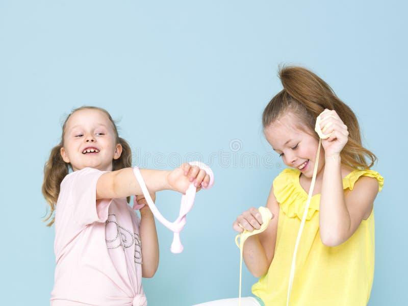 Twee mooie meisjes die met eigengemaakt slijm spelen en heel wat pret voor blauwe achtergrond hebben stock foto's