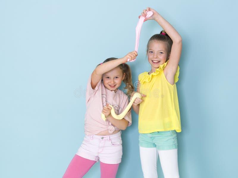Twee mooie meisjes die met eigengemaakt slijm spelen en heel wat pret voor blauwe achtergrond hebben royalty-vrije stock foto's