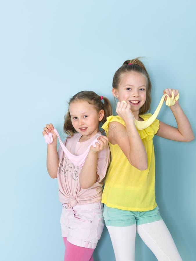 Twee mooie meisjes die met eigengemaakt slijm spelen en heel wat pret voor blauwe achtergrond hebben royalty-vrije stock afbeeldingen