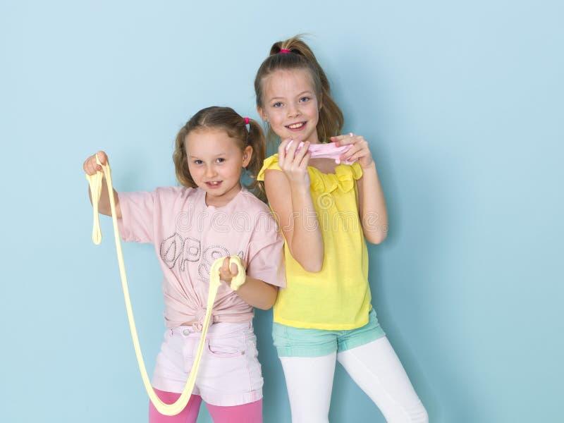 Twee mooie meisjes die met eigengemaakt slijm spelen en heel wat pret voor blauwe achtergrond hebben stock afbeeldingen
