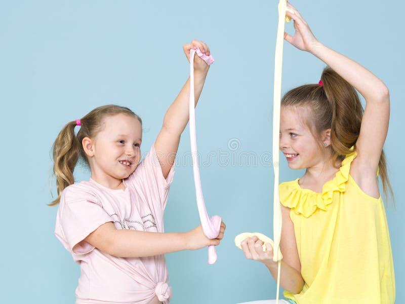 Twee mooie meisjes die met eigengemaakt slijm spelen en heel wat pret voor blauwe achtergrond hebben stock fotografie