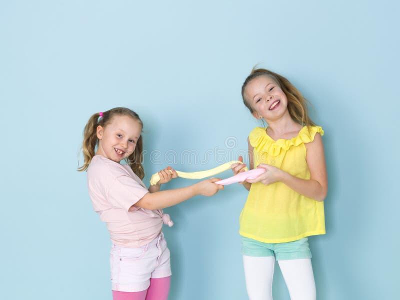 Twee mooie meisjes die met eigengemaakt slijm spelen en heel wat pret voor blauwe achtergrond hebben stock afbeelding