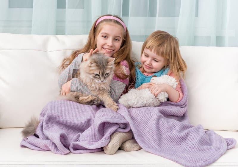 Twee mooie meisjes die op bank omhelzen royalty-vrije stock foto
