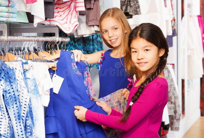 Twee mooie meisjes die samen in de opslag winkelen stock afbeelding