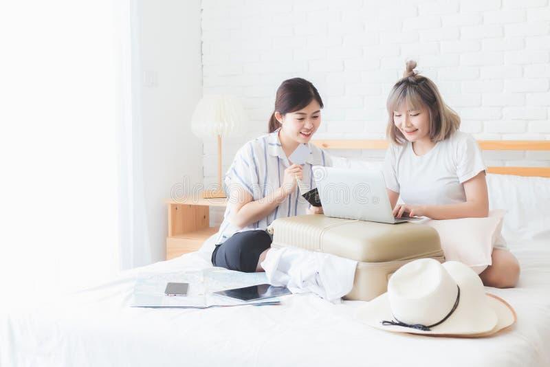 Twee mooie meisjes helpen elkaar van plan zijn om aanpassing en vliegtuigkaartjes op notitieboekjecomputers, reispakketten te boe royalty-vrije stock foto