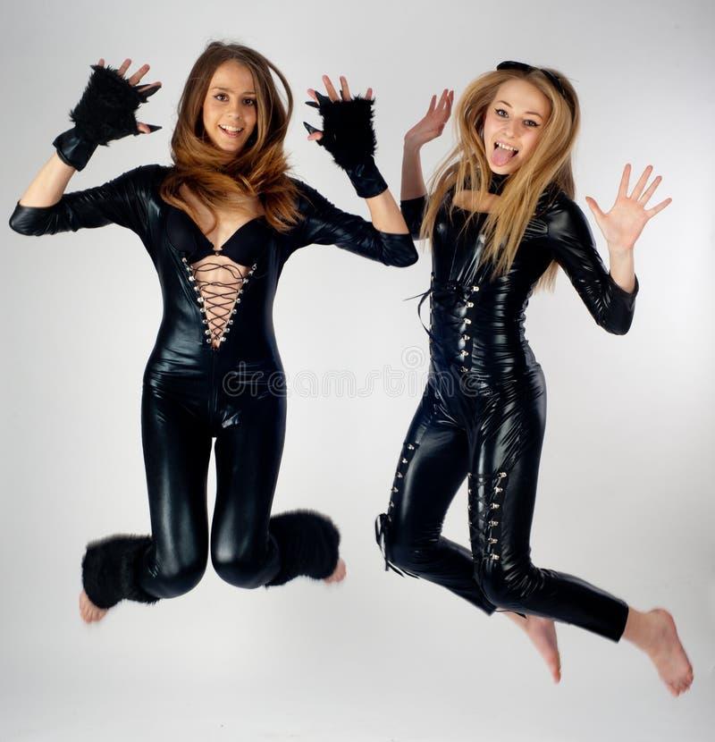 Twee mooie meisjes in kattenkostuums het springen royalty-vrije stock afbeeldingen