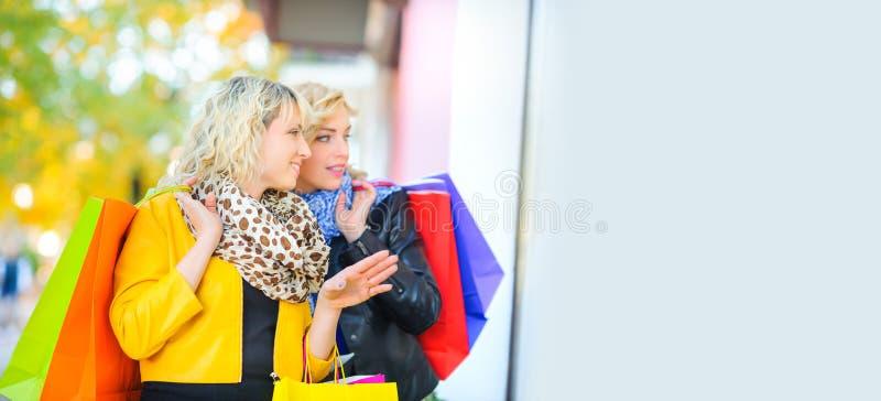 Twee mooie meisjes met het winkelen zakken bevinden zich op de straat dichtbij het winkelvenster stock foto