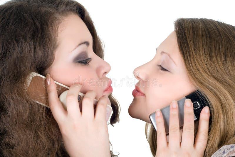 Twee mooie meisjes met telefoons royalty-vrije stock afbeeldingen