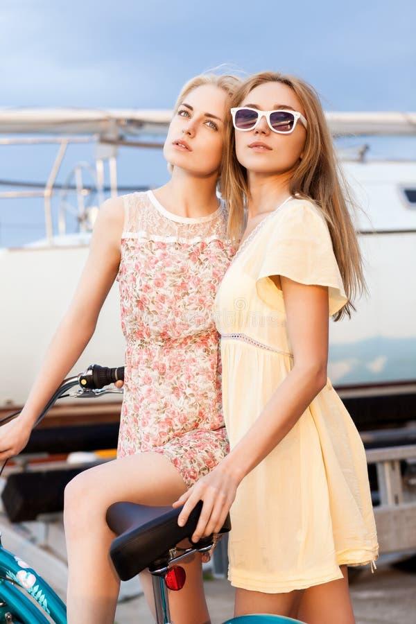 Twee mooie meisjes op zee pijler stock afbeelding