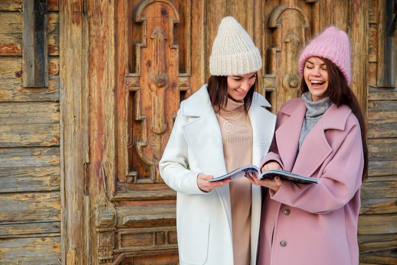 Twee mooie meisjes in openlucht gelezen tijdschrift en glimlach stock foto's