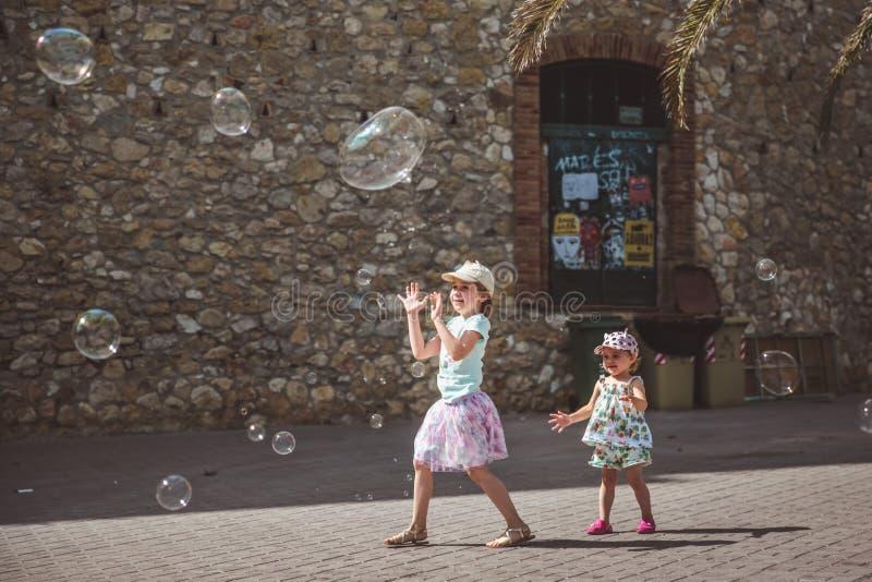 Twee mooie meisjes spelen met grote bellen in straat in de zomerdag stock foto's