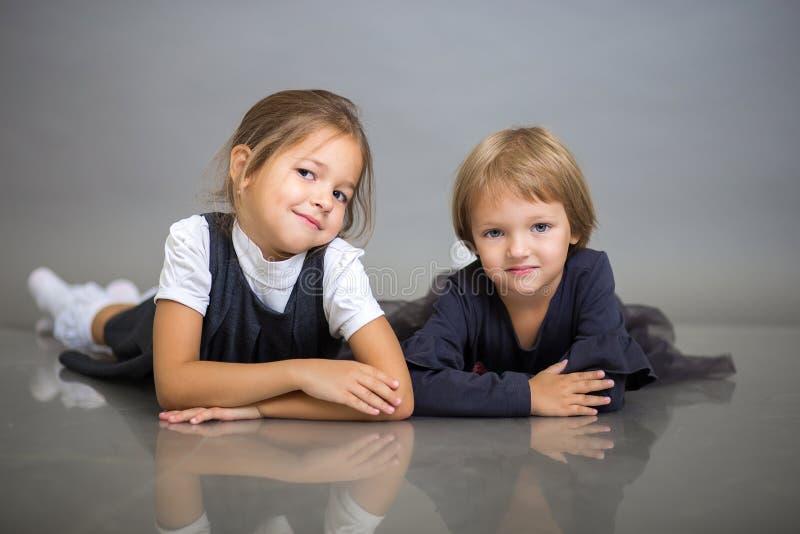 Twee mooie meisjes van de kleine zuster stellen het liggen op een grijze achtergrond royalty-vrije stock afbeeldingen