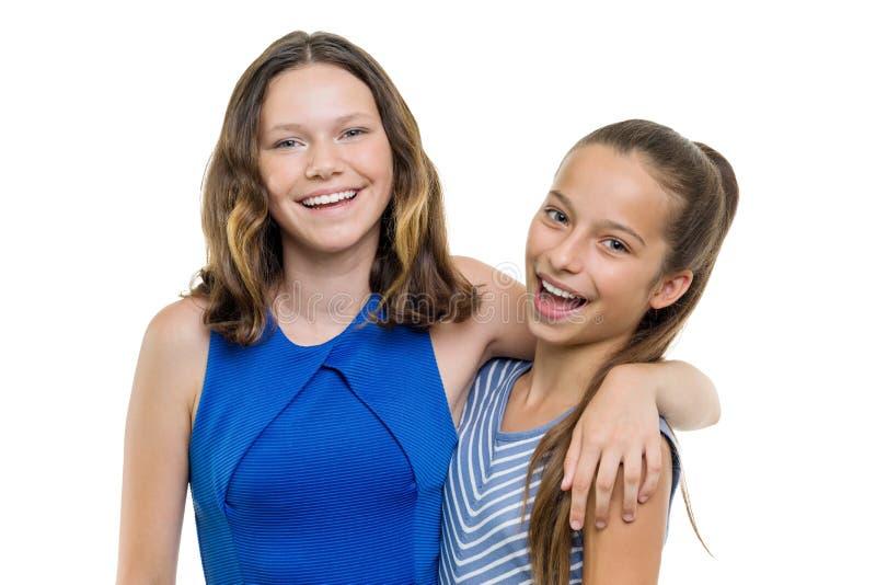 Twee mooie meisjesglimlach met perfecte witte die glimlach, op witte achtergrond wordt geïsoleerd stock afbeelding