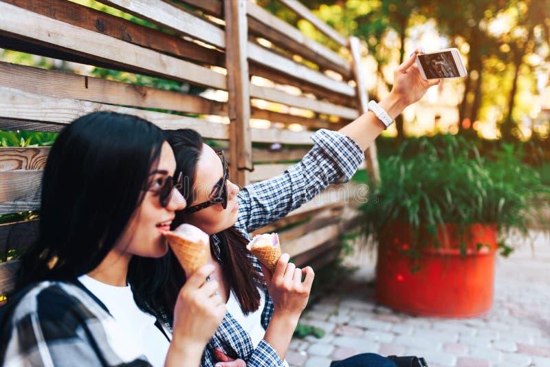 Twee mooie roomijs eten en vrouwen die selfie maken stock afbeelding