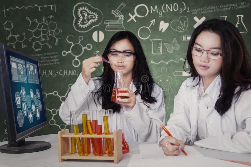Twee mooie studenten die in laboratorium werken stock foto's