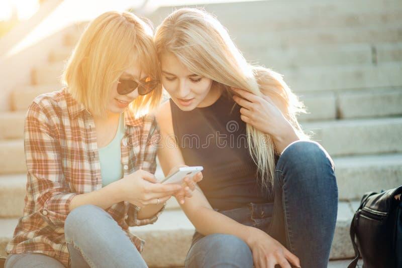 Twee mooie studenten die media op inhoud online in slimme telefoon in park letten royalty-vrije stock afbeeldingen