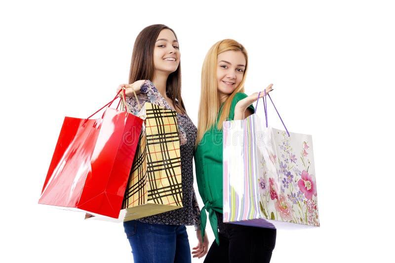Twee mooie tieners die het winkelen zakken houden stock afbeelding