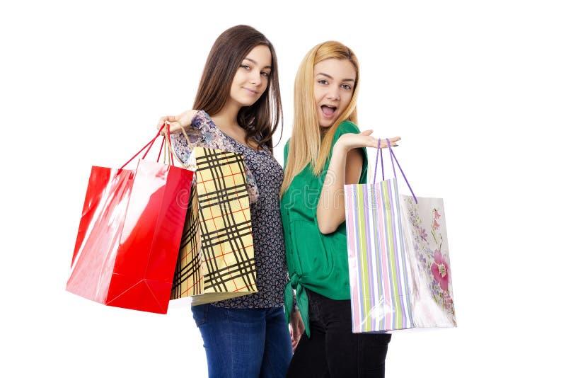 Twee mooie tieners die het winkelen zakken houden stock foto's