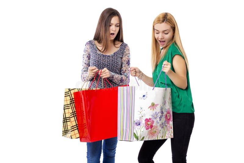 Twee mooie tieners die in hun het winkelen zakken kijken stock fotografie