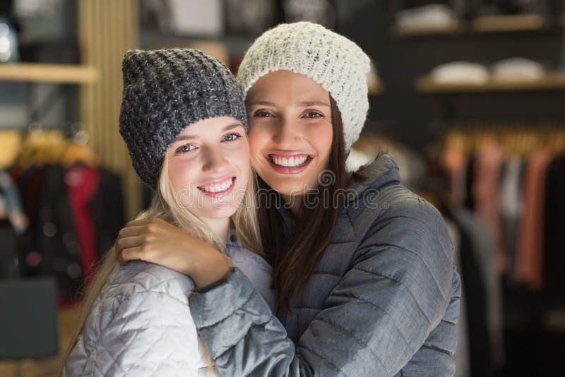 Twee mooie vrienden die met de winterkleren bij camera glimlachen stock foto