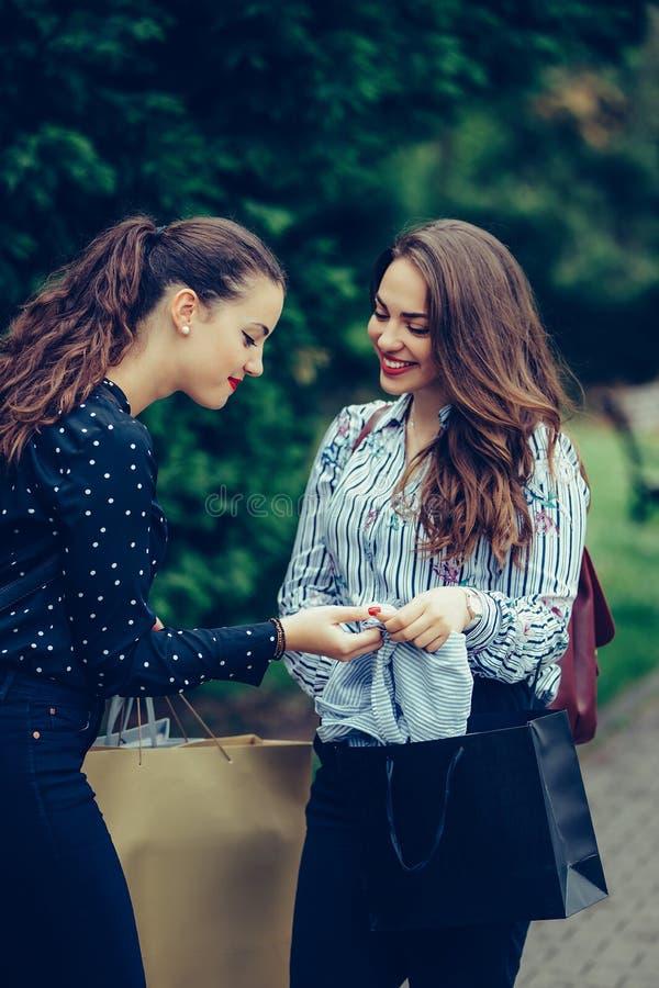 Twee mooie vrouwen die in het park na het winkelen lopen en hun nieuwe aankopen met elkaar delen royalty-vrije stock afbeelding