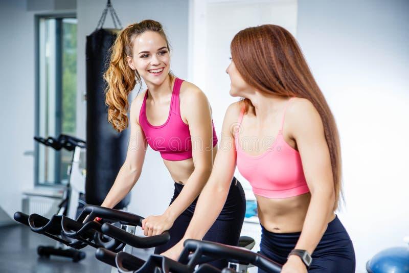 Twee mooie vrouwen die oefeningen op fietsen doen bij de gymnastiek royalty-vrije stock afbeelding