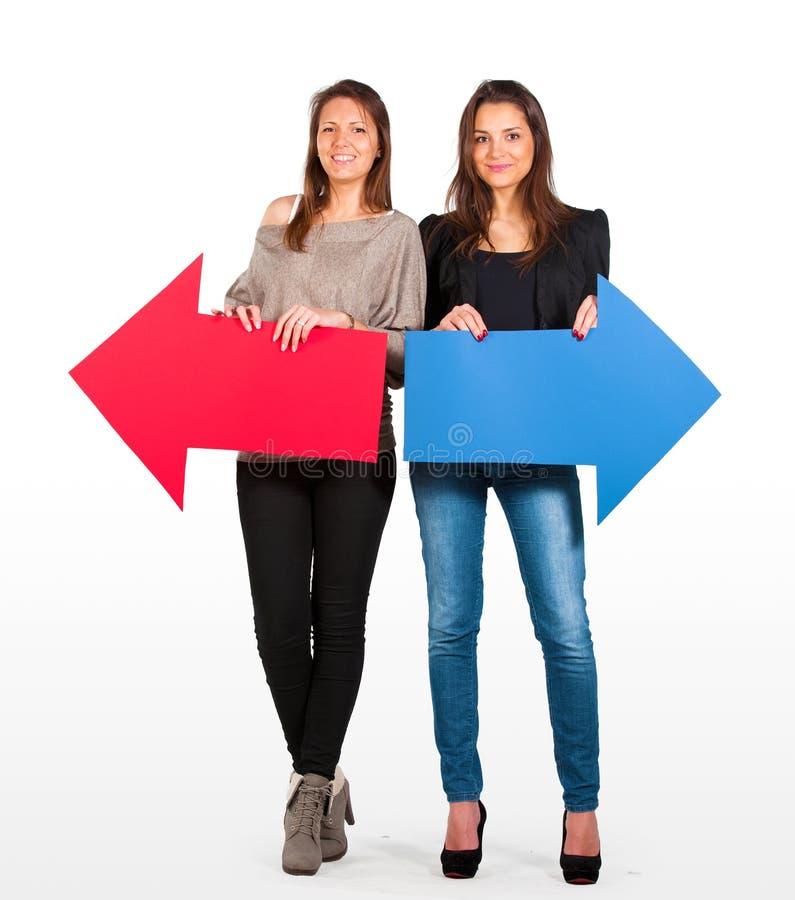 Twee mooie vrouwen die rode en blauwe pijl houden, links en net stock fotografie