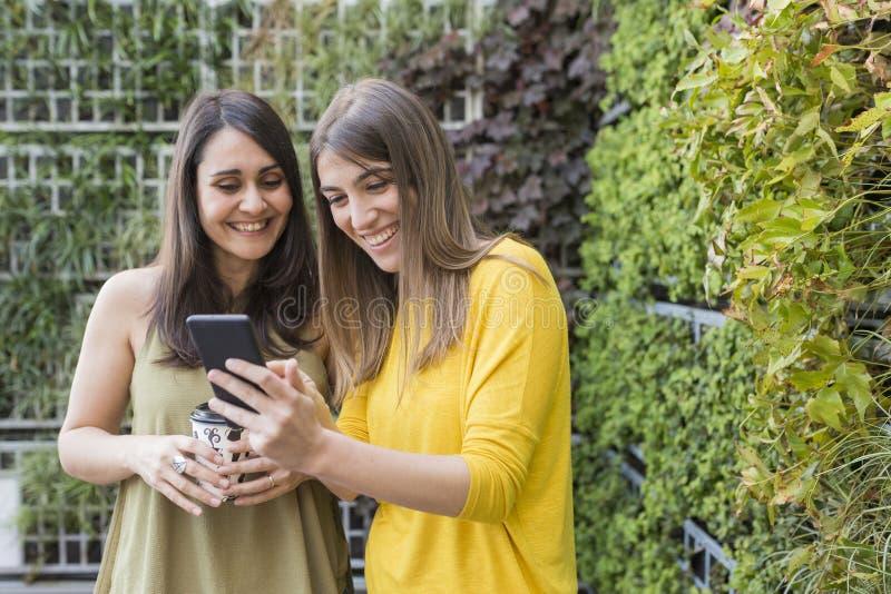 Twee mooie vrouwen die selfie met mobiele telefoon nemen Groene Achtergrond Men houdt een kop van koffie Zij lachen en royalty-vrije stock fotografie