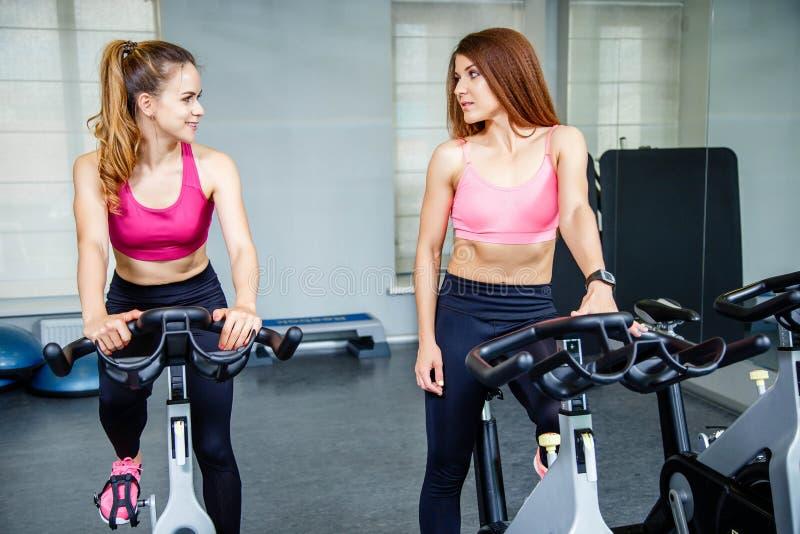 Twee mooie vrouwen, die in sportkleding dragen, die binnen biking oefening doen royalty-vrije stock foto