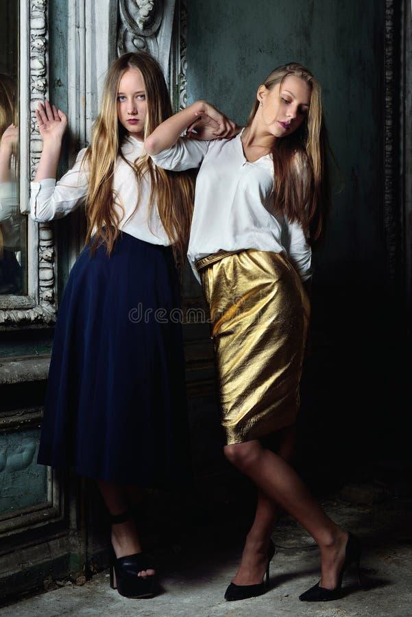 Twee mooie vrouwen die in verouderd binnenland stellen. stock afbeelding