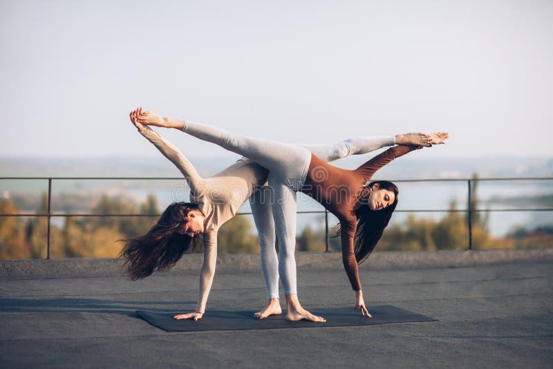 Twee mooie vrouwen die yogaasana Ardha Chandrasana doen stock afbeeldingen