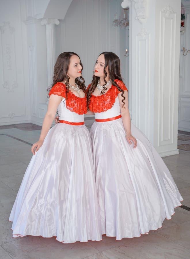 Twee Mooie vrouwen middeleeuwse kleding met hoepelrok in de zaal stock fotografie
