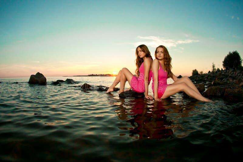 Twee mooie vrouwen op het strand bij zonsondergang. Geniet van aard. Luxe royalty-vrije stock foto's