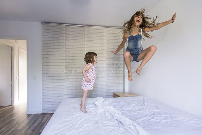 Twee mooie zusterjonge geitjes die en op bed thuis spelen springen Pret binnen Familieliefde en levensstijl royalty-vrije stock fotografie