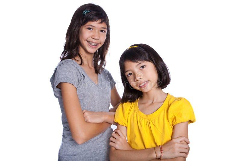 Twee mooie zusters in studioportret stock foto's