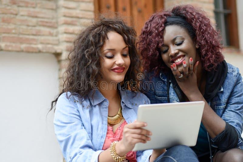 Twee mooie zwarte meisjes met tabletcomputer in stedelijke backgrun royalty-vrije stock foto's