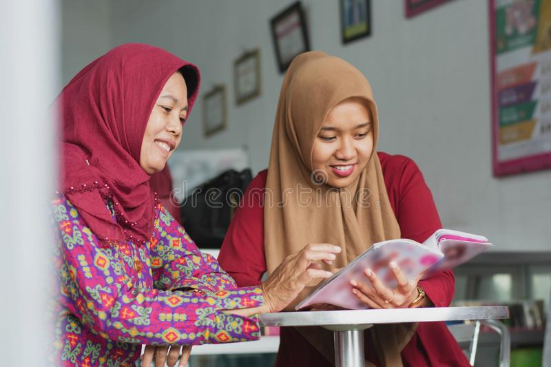 Twee Moslimhijab vrouw die een tijdschriftzitting binnen hun manieropslag lezen royalty-vrije stock foto's